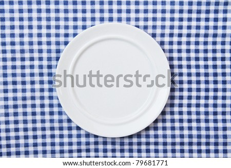 White Plate on Blue and White checkered Fabric Tablecloth Background - stock photo