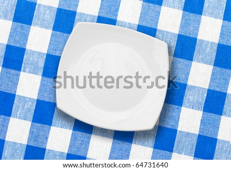 white plate on blue checked fabric tablecloth - stock photo