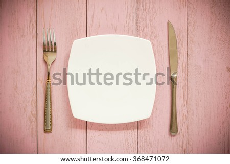 white plate, vintage fork and knife  on rustic pink wooden table. Top view point. - stock photo