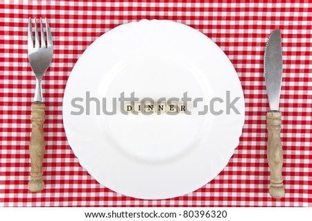 White plate with Dinner-lettering and cutlery - stock photo