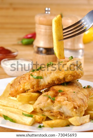 White plate with fish and chips, mayo and ketchup - stock photo