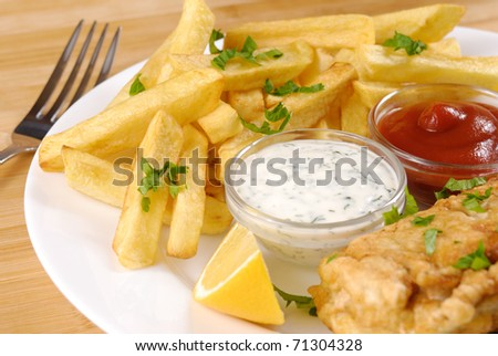 White plate with fish and chips, mayo, lemon and ketchup