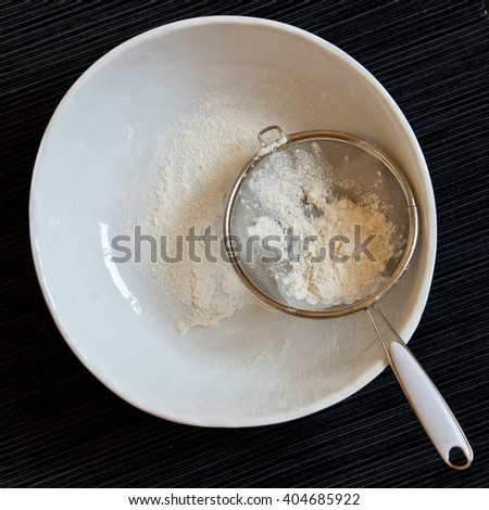 White plate with flour sifted through a colander on a black background, top view