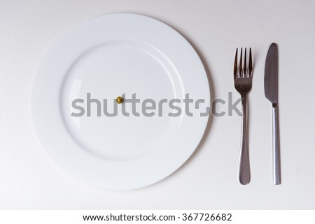 White plate with fork and knife lying on a white background - stock photo