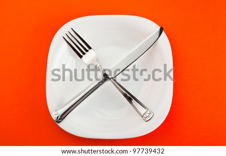 white plate with fork and knife on paper