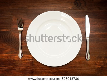 White plate with fork and knife on wooden table