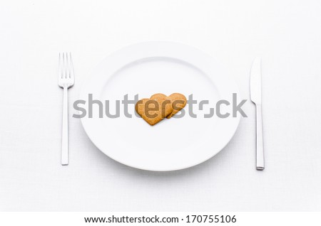 white plate with fork and knife with two gingerbread hearts isolated on white background.