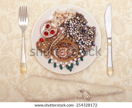 White plate with jewelry treasure diamonds on it symbolizing women greed and mercantilism - stock photo