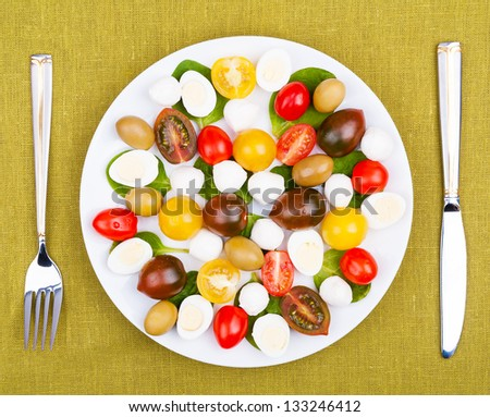 White plate with salad on the background of a linen tablecloth