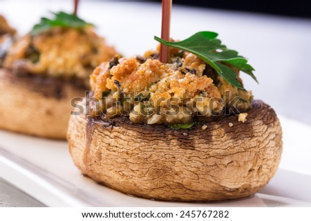 White plate with stuffed mushroom caps. Champignon filled with cheese and nuts. - stock photo