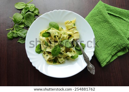 White plate with tagliatelle pasta with fresh spinach