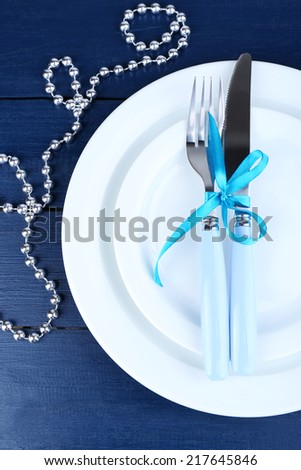 White plates, fork, knife, napkin and Christmas decoration on wooden background - stock photo