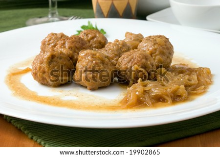 white platter with meat balls on onions sauce