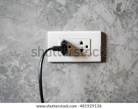 white plug socket on the room wall