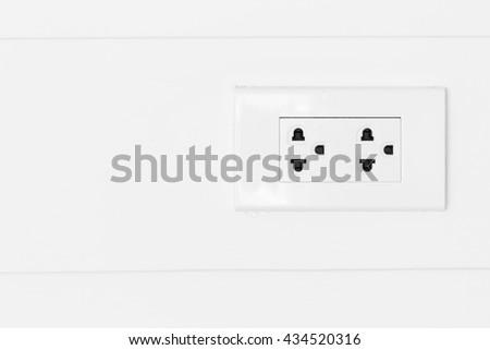 White plugs on white wood wall, plug copy space, plug socket, plug electric, plug outlet, plug switch, plug backdrop, plug background. - stock photo