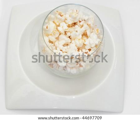 White popcorns on white plate on white background - stock photo