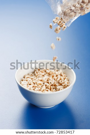 White popped wheat flakes pouring from plastic bag into plate - stock photo
