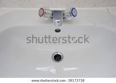 white porcelain bathroom hand wash basin with chrome tap over - stock photo