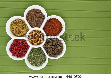 White porcelain bowl with spices on green background - stock photo