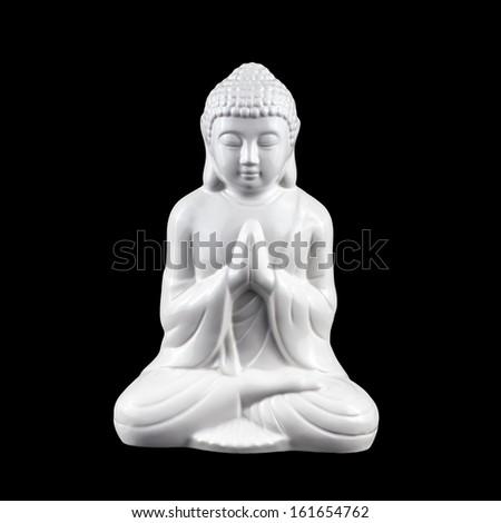 White, porcelain statuette of sitting meditating Buddha isolated on black - stock photo
