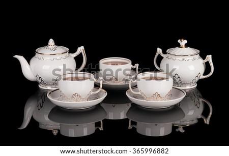 White porcelain tea set on black reflecting background - stock photo