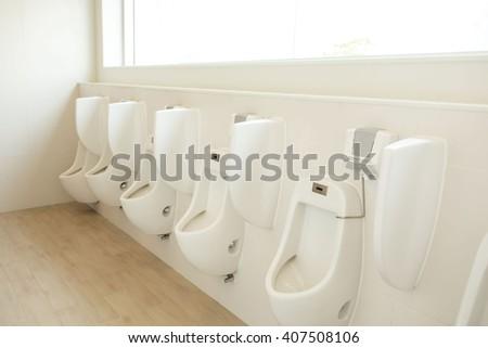 white porcelain urinals in public toilets  for men  - stock photo