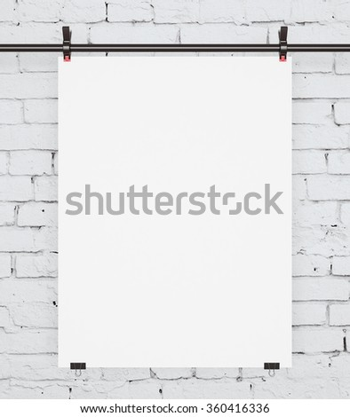 white poster sandwiched metal clasps on brick wall - stock photo