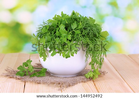 White pot with parsley and dill on wooden table on natural background - stock photo