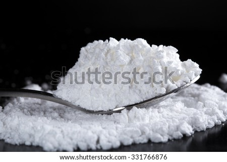 White powder in silver spoon over dark background - stock photo