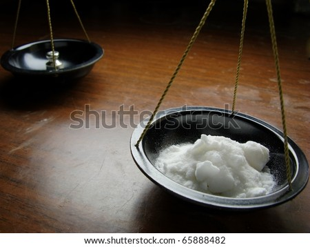 White powder on pharmaceutical scales - stock photo