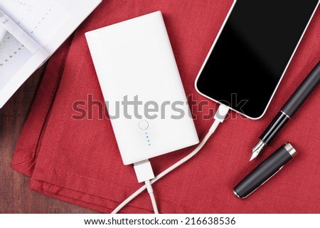 white power bank charging smart phone - stock photo