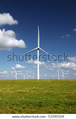 White power generating wind turbines, windmills against  blue sky, yellow wildflowers, on agricultural green pastures