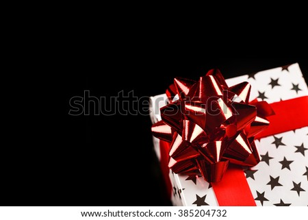 White present box with silver stars on it, with red shine tape and bow-knot, with gift inside, isolated on black bachground. - stock photo