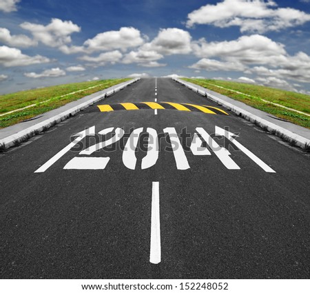 White print arrows and 2014 on an asphalt road, approaching a speed ramp vanishing into the horizon of blue cloudy sky, for the concept of challenges ahead for new year 2014. - stock photo