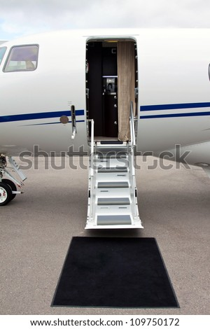 white private jet and open ladder, black carpet at the airport on a background cloudy sky - stock photo