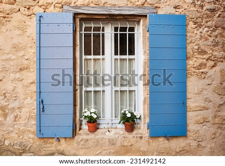 White Provence window with blue covers and pots of flowers in Grambois village, South France - stock photo