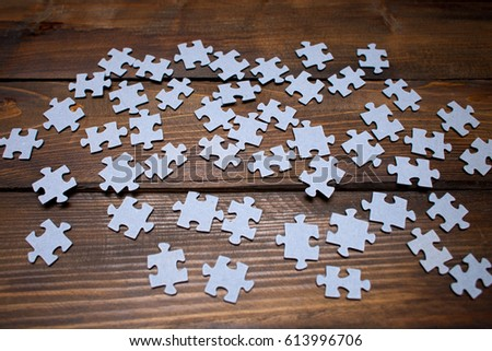 White puzzles from a mosaic on wooden background. Top view.