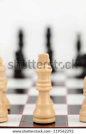 White queen standing at the chessboard against white background