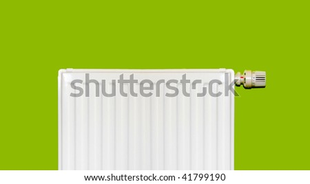 White radiator with thermostat on green wall - stock photo