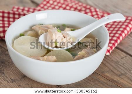 White radish chicken soup in white bowl. - stock photo