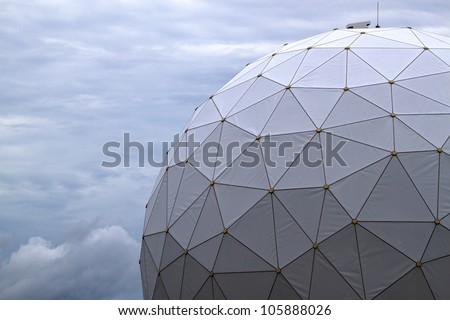 White radome covering sensitive tracking equipment at Kennedy Space Center is shot against a darkening Florida sky. - stock photo