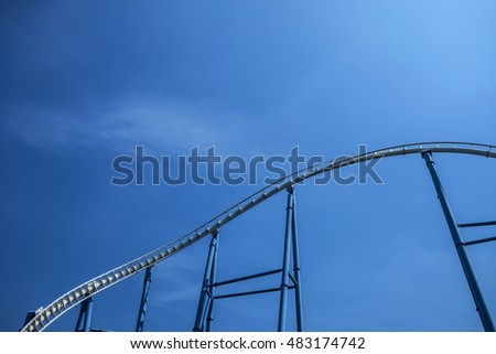 white rail tracks of steel roller coaster with blue steel supporting tubular against blue sky