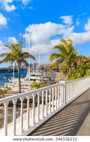 White railing and palm trees in Puerto Calero marina built in Caribbean style, Lanzarote island, Spain  - stock photo