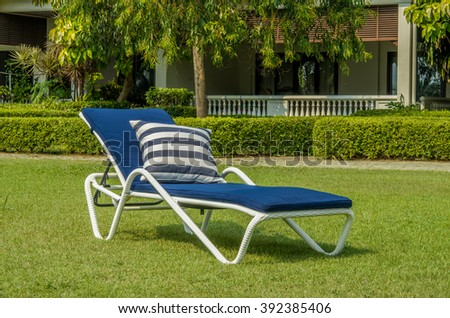 White rattan sun lounger with blue cushion and pillow in the garden - stock photo