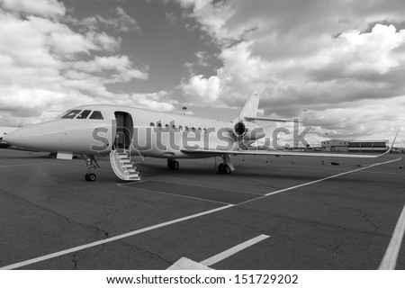 White reactive private jet, the front landing gear and a ladder on blue sky and clouds - stock photo