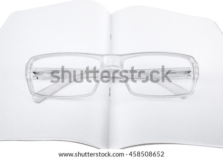 White Reading Glasses Frames on Top of The Book  - stock photo