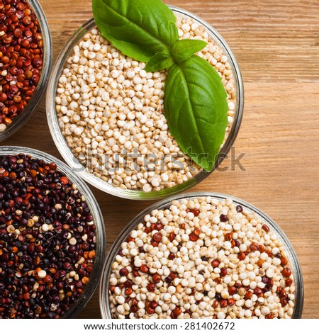 White, red, black and mixed raw quinoa, South American grain, in glass bowls with basil leaves on old rustic wooden background. Top view.  - stock photo