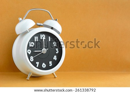 White retro alarm clock on light brown background with copy space - stock photo