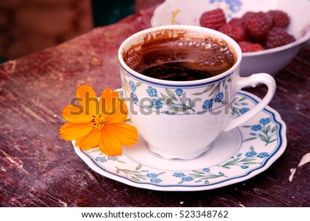 White retro cup of coffee with orange Cosmea (Cosmic) flower on the dark red table