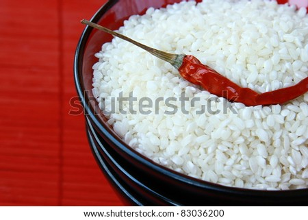 white rice in a black bowl with chili pepper on  red background - stock photo